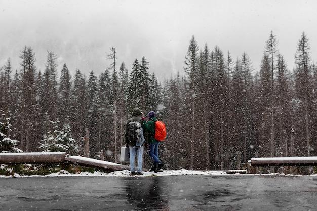 Coppie dei turisti con gli zainhi che stanno nella foresta nevosa di inverno e che considerano gli alberi.