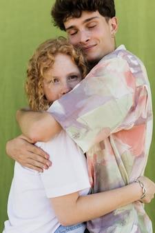 Coppie del colpo medio che abbracciano con il fondo verde