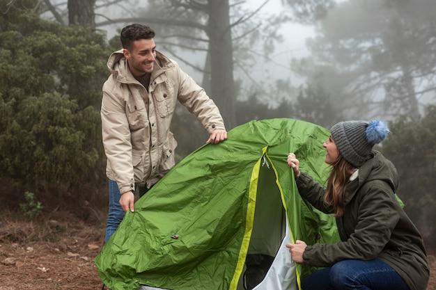 Coppie del colpo medio che mettono su una tenda