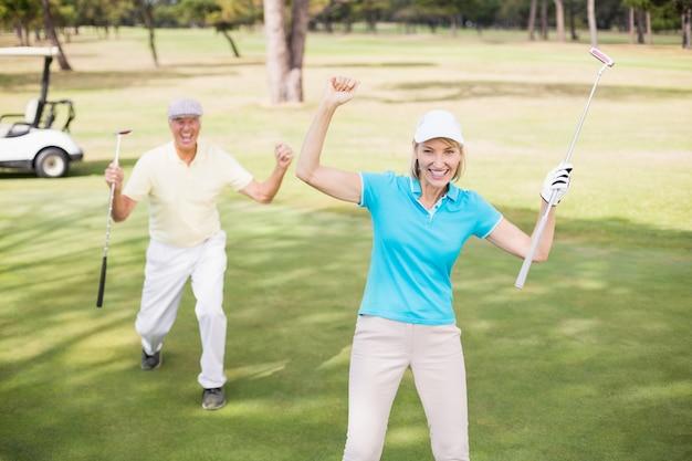 Coppie del giocatore di golf che celebrano successo mentre stando sul campo