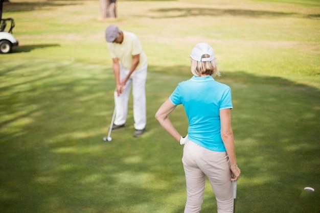 Coppie del giocatore di golf che stanno sul campo