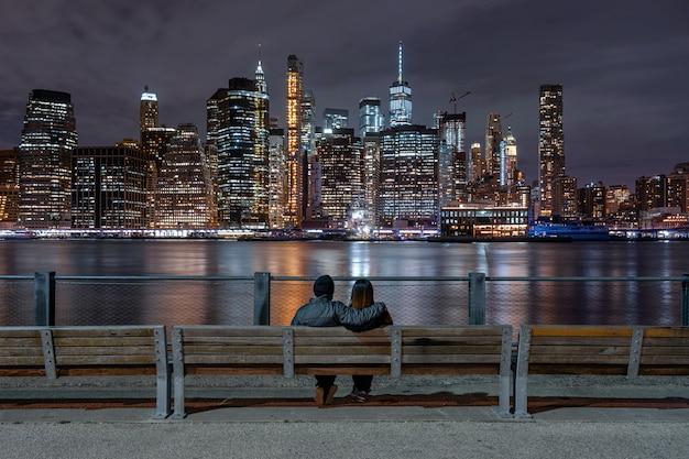 Coppie del lato posteriore che si siedono e che guardano paesaggio urbano di new york accanto al fiume orientale alla notte