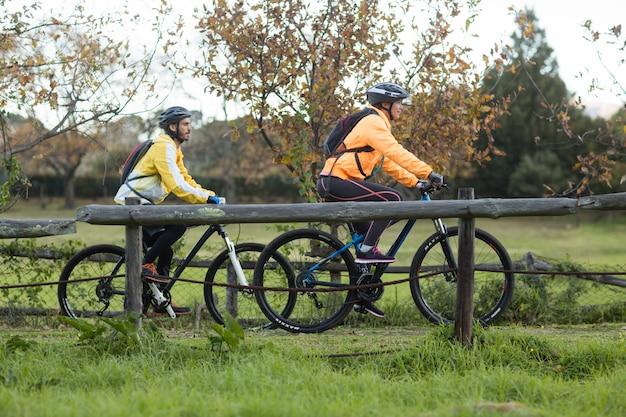 Coppie del motociclista che ciclano nella campagna