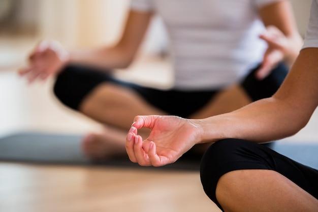 Coppie del primo piano che esercitano yoga
