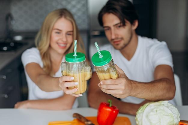 Coppie del primo piano che rasano un vetro con i frullati. concetto di cibo sano.
