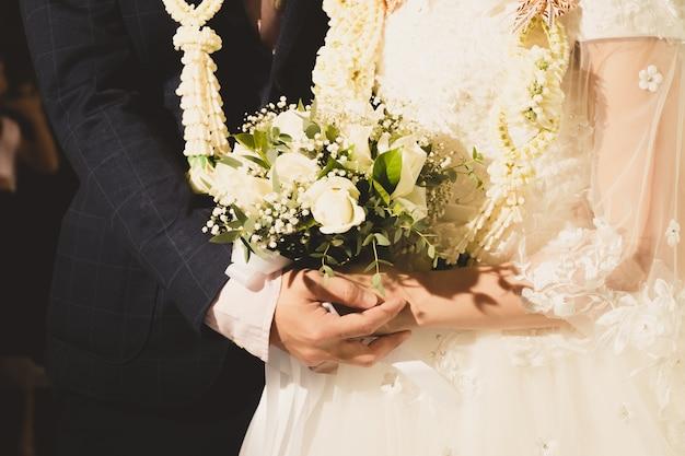 Coppie del primo piano, sposa e sposo nella cerimonia di nozze in piedi insieme a felice.