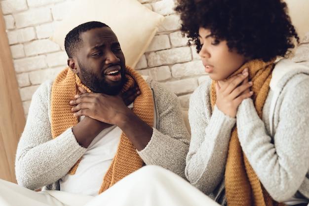 Coppie dell'afroamericano con mal di gola che si siedono sul letto.