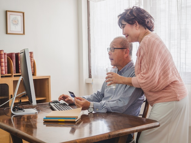 Coppie dell'anziano che per mezzo del computer insieme alla carta di credito a casa