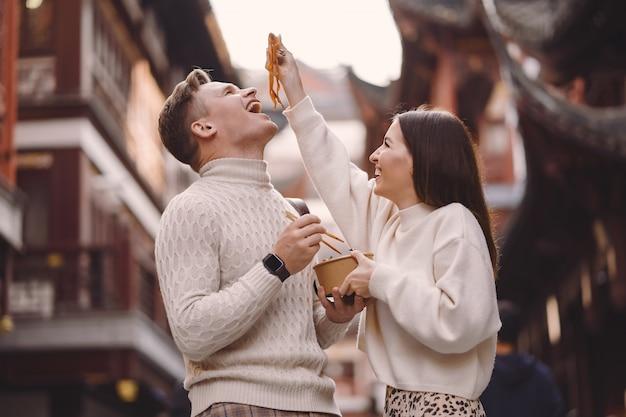 Coppie della persona appena sposata che mangiano le tagliatelle con le bacchette a shanghai fuori di un mercato dell'alimento