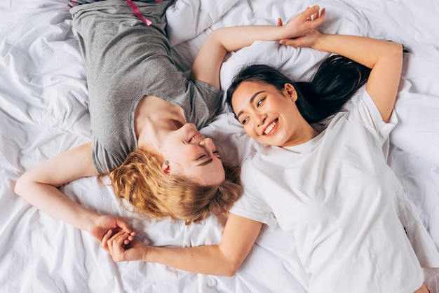 Coppie delle donne che ridono e che tengono le mani che si trovano a letto