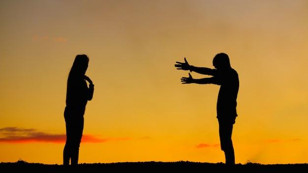 Coppie delle siluette sul cielo al tramonto