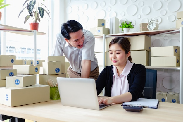 Coppie di affari di stile di vita che si siedono nell'ufficio che guarda funzionamento felice del computer portatile dello schermo, piccola impresa della pmi