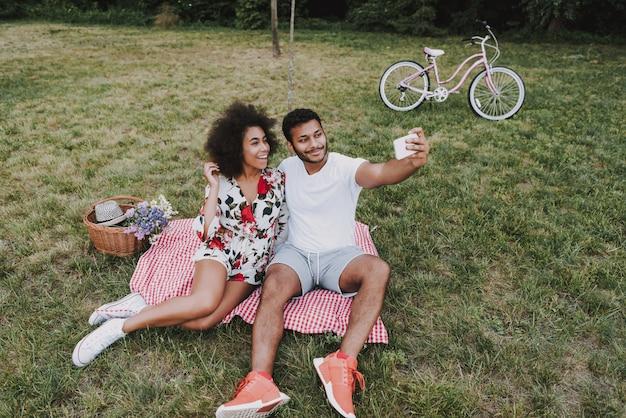Coppie di afro che fanno selfie su un picnic.