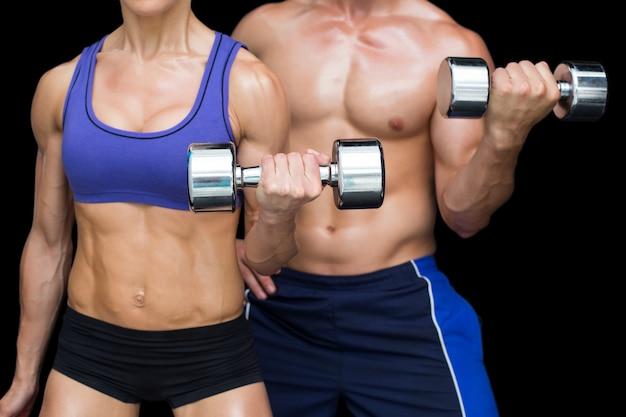 Coppie di bodybuilding in posa con grandi manubri