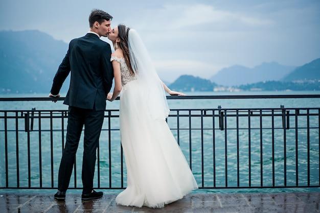 Coppie di cerimonia nuziale che baciano sullo sfondo di un lago e montagne