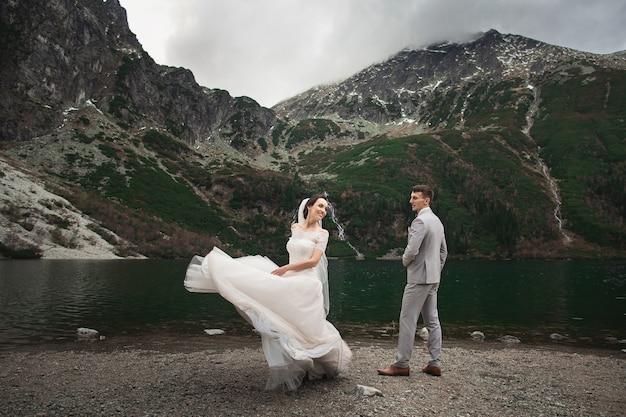 Coppie di cerimonia nuziale che camminano vicino al lago in montagne di tatra in polonia. morskie oko.