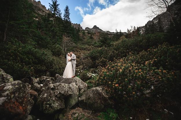 Coppie di cerimonia nuziale che camminano vicino al lago in montagne di tatra in polonia.