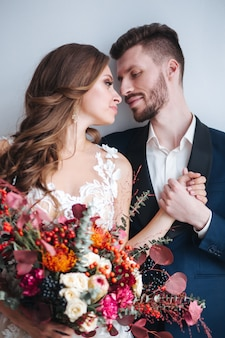 Coppie di cerimonia nuziale con il mazzo della holding della sposa. sensuale ritratto di una giovane coppia. foto del matrimonio al coperto