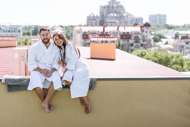 Coppie di flirt con spumante su un tetto