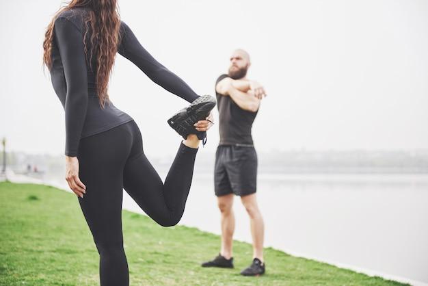Coppie di forma fisica che allungano all'aperto nel parco vicino all'acqua. giovane uomo e donna barbuti che si esercitano insieme nella mattina