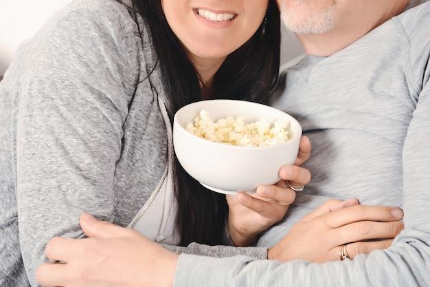 Coppie di mezza età che abbracciano e che mangiano popcorn