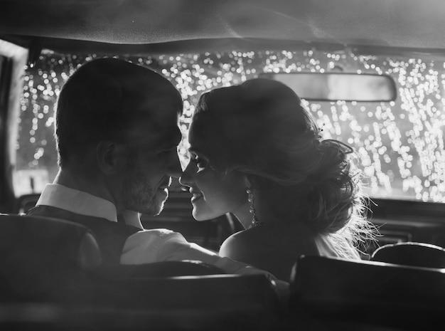 Coppie di nozze che baciano in retro automobile