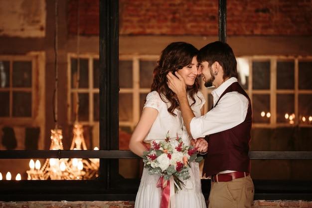 Coppie di nozze che baciano nell'interno del sottotetto