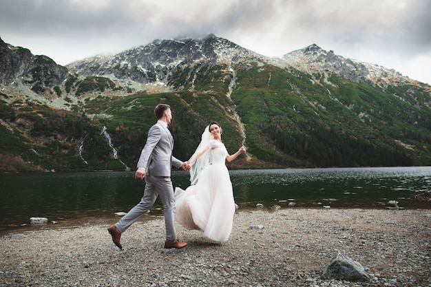 Coppie di nozze che corrono vicino al lago in montagne di tatra in polonia, morskie oko