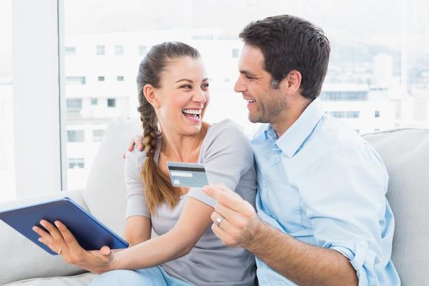 Coppie di risata che si siedono sul divano che compera online con il pc della compressa