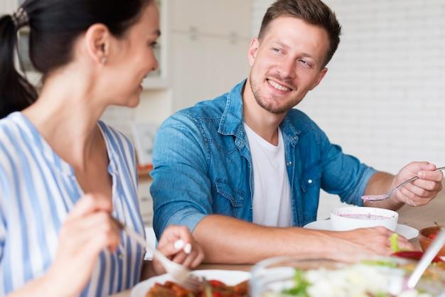 Coppie di vista laterale che mangiano insieme