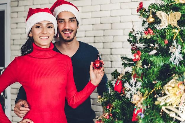 Coppie dolci romantiche in cappelli di santa divertendosi decorando l'albero di natale e sorridendo mentre celebrando la notte di san silvestro