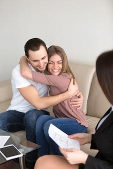 Coppie emozionanti che abbracciano sulla riunione con l'agente immobiliare, investimento di ipoteca