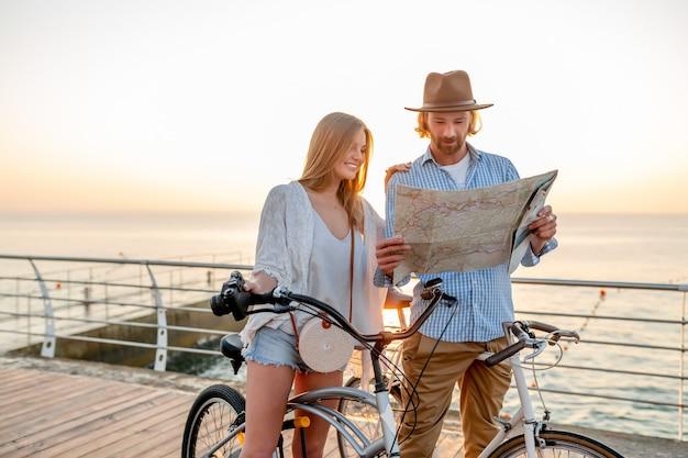 Coppie felici attraenti che viaggiano in estate sulle biciclette, uomo e donna con moda stile hipster boho capelli biondi divertirsi insieme, guardando nella mappa visite turistiche