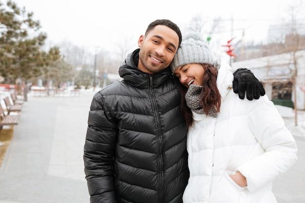 Coppie felici che abbracciano e che ridono nel parco di inverno