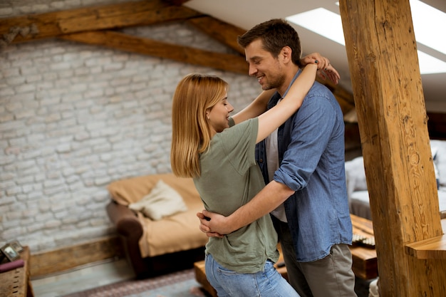 Coppie felici che abbracciano nell'appartamento loft