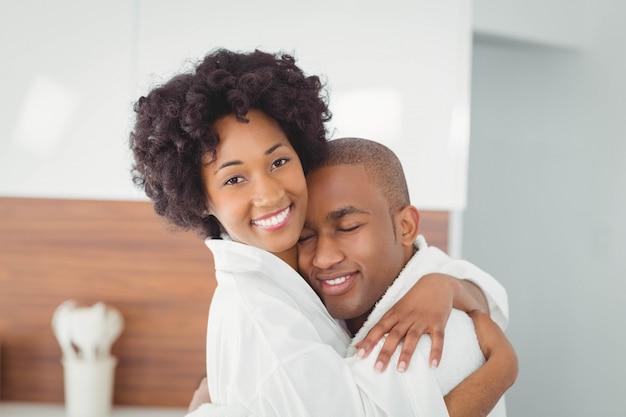 Coppie felici che abbracciano nella cucina a casa