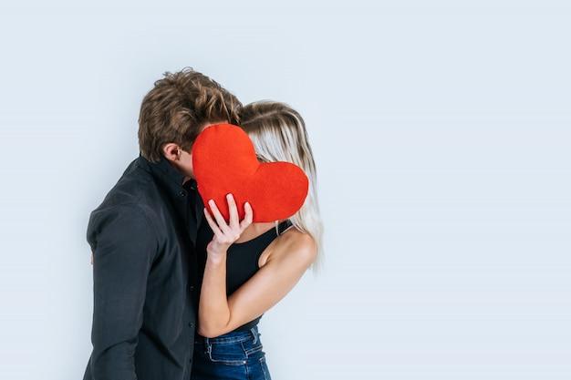 Coppie felici che amano insieme tenendo un cuore rosso