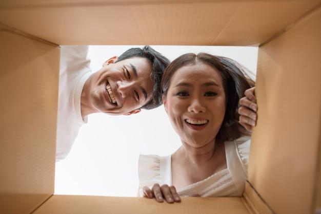 Coppie felici che aprono una scatola e che guardano dentro al prodotto