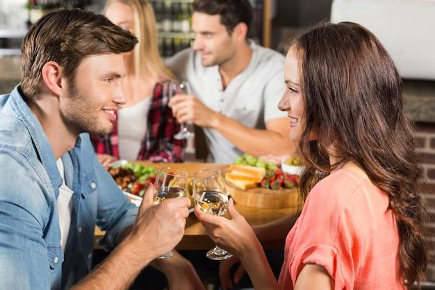 Coppie felici che bevono vino bianco