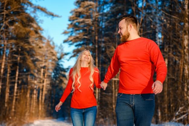 Coppie felici che camminano nella foresta nevosa