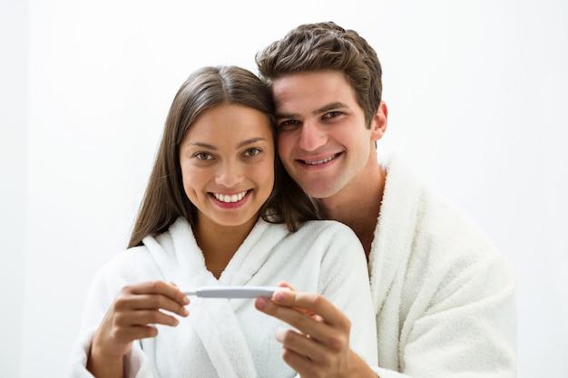 Coppie felici che controllano test di gravidanza