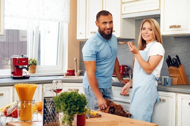Coppie felici che cucinano cibo in cucina con il loro cane