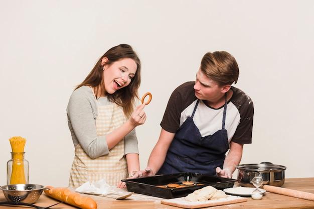 Coppie felici che cucinano gli anelli di pane