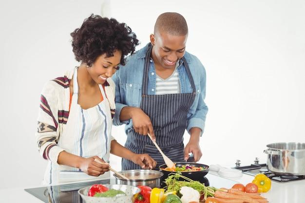Coppie felici che cucinano insieme le verdure