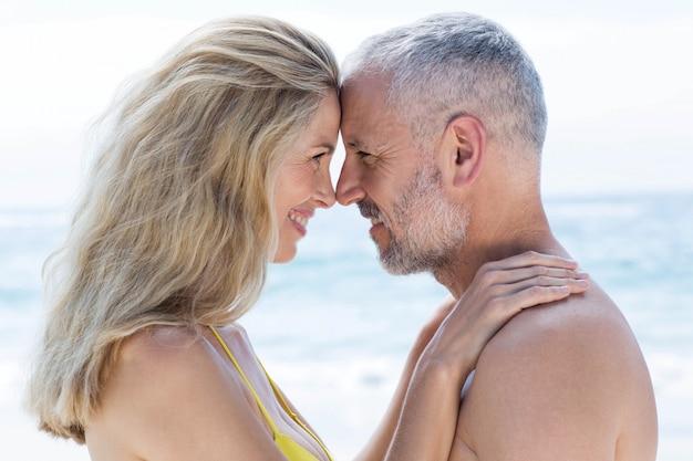 Coppie felici che fanno una pausa il mare e che sorridono a vicenda
