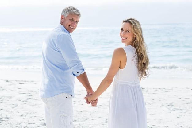 Coppie felici che fanno una pausa il mare e che tengono le mani