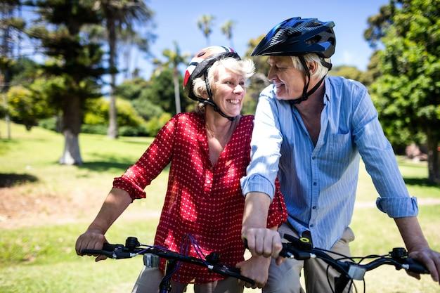Coppie felici che guidano una bicicletta in parco