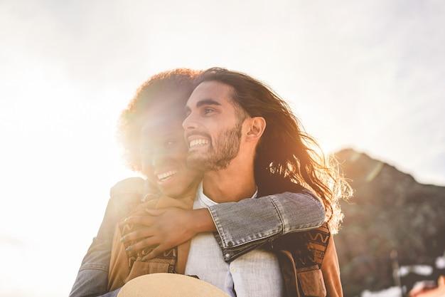 Coppie felici che hanno momenti teneri all'aperto al tramonto - giovani amanti divertendosi insieme - amore, relazione e concetto etnico di muti - fuoco sull'uomo