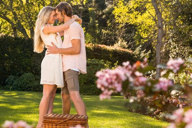 Coppie felici che hanno un picnic e che abbracciano nel giardino