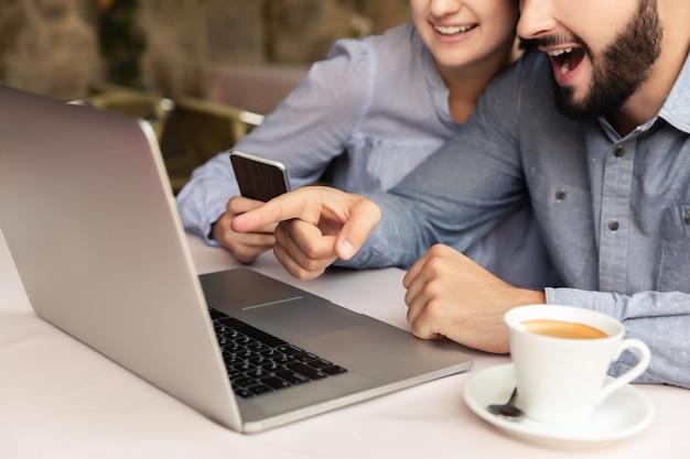Coppie felici che lavorano a casa, uomo e donna che lavorano al computer portatile all'interno